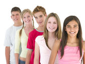 Five friends in a row smiling — Stock Photo