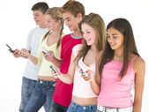 Row of five friends using cellular phones smiling — Foto de Stock