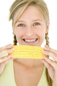 Teenage girl holding corn on cob and smiling — Stock Photo