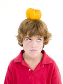Young boy with yellow pepper on his head frowning — Stock Photo
