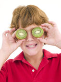 Young boy holding kiwi halves over eyes smiling — Stock Photo