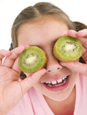 Young girl holding kiwi halves over eyes smiling — Stock Photo