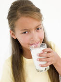 Young girl drinking glass of milk — Stock Photo