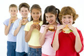 Row of five young friends eating hamburgers — Stock Photo
