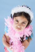 Young girl wearing crown and feather boa frowning — Stock Photo
