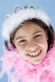 Young girl wearing crown and feather boa smiling — Stock Photo
