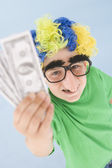 Young boy wearing clown wig and fake nose holding money — Stock Photo