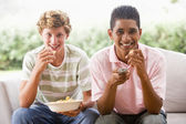 Teenage Boys Sitting On Couch Eating crisps Together — Stock Photo