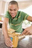 """Adolescent mâle faisant au beurre d'arachide """"sandwich — Photo"""