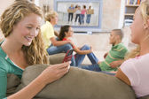Teenagers Hanging Out In Front Of Television Using Mobile Phones — Stock Photo