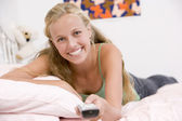 Teenage Girl Lying On Her Bed Changing Television Channels — Stock Photo