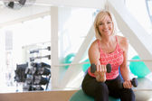 Woman Using Hand Weights On Swiss Ball At Gym — Stock Photo