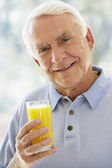 Man Smiling At Camera And Drinking Orange Juice — Stock Photo