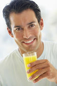 Mid Adult Man Smiling At The Camera And Drinking Orange Juice — Stock Photo