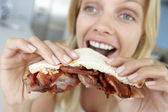 Mid Adult Woman Eating Bacon Sandwich — Stock Photo