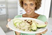 Połowie dorosła kobieta trzymając płytkę ze zdrową żywnością — Zdjęcie stockowe