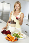 Mid Adult Woman Making Fresh Vegetable Juice — Stock Photo