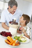 Father And Son Making Fresh Vegetable Juice — Stock Photo
