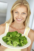 Mid Adult Woman Holding A Plate Of Broccoli — Stock Photo