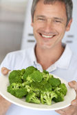 Middle Aged Man Holding A Plate Of Broccoli — Stok fotoğraf