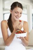 Jonge vrouw een kom verse aardbeien eten — Stockfoto