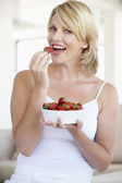 Mid Adult Woman Eating A Bowl Of Strawberries — Stock Photo