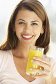 Mid Adult Woman Holding A Glass Of Orange Juice, Smiling At The — Stock Photo