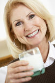 Senior Woman Holding A Glass Of Milk, Smiling At The Camera — Stock Photo