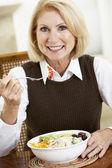 Senior Woman Eating Dinner, Smiling At The Camera — Stock Photo