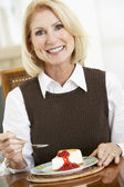 Senior Woman Eating Cheesecake — Stock Photo