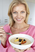 Mid Adult Woman Eating Porridge With Fresh Fruit — Stock Photo