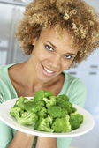 Mid Adult Woman Holding A Plate Of Broccoli, Smiling At The Came — Stock Photo