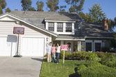 Семья, стоя вне дома с недвижимостью знак — Стоковое фото