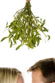 Couple standing beneath mistletoe — Stock Photo