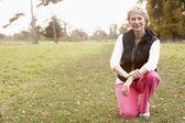 Kadın parkta crouching kıdemli portresi — Stok fotoğraf