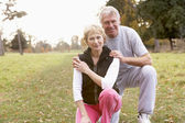 Portrait Of Senior Couple Crouching In The Park — Stok fotoğraf