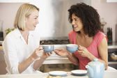 Female Friends Enjoying Tea And Cookies At Home — Stock Photo