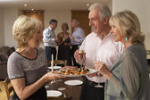 Woman Serving Hors D'oeuvres To Her Guests At A Dinner Party — Stockfoto
