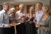 Man Serving Hors D'oeuvres To His Guests At A Dinner Party — Stock Photo