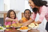 Moeder een maaltijd serveren aan haar kinderen thuis — Stockfoto