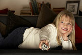 Young Girl Using Television Remote Control — Stock Photo