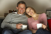 Couple With Coffee Mugs Watching Television — Stock Photo