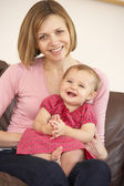 Mother And Baby Daughter On Sofa — Stockfoto