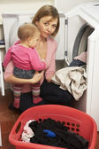 Woman Doing Laundry And Holding Baby Daughter — Stock Photo