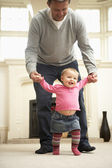 Father Helps Baby Daughter With Walking — Stock Photo