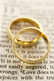 Dos anillos de boda descansando en una página de la Biblia — Foto de Stock