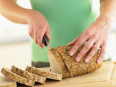 Woman Slicing Mixed Grain Bread — Stock Photo