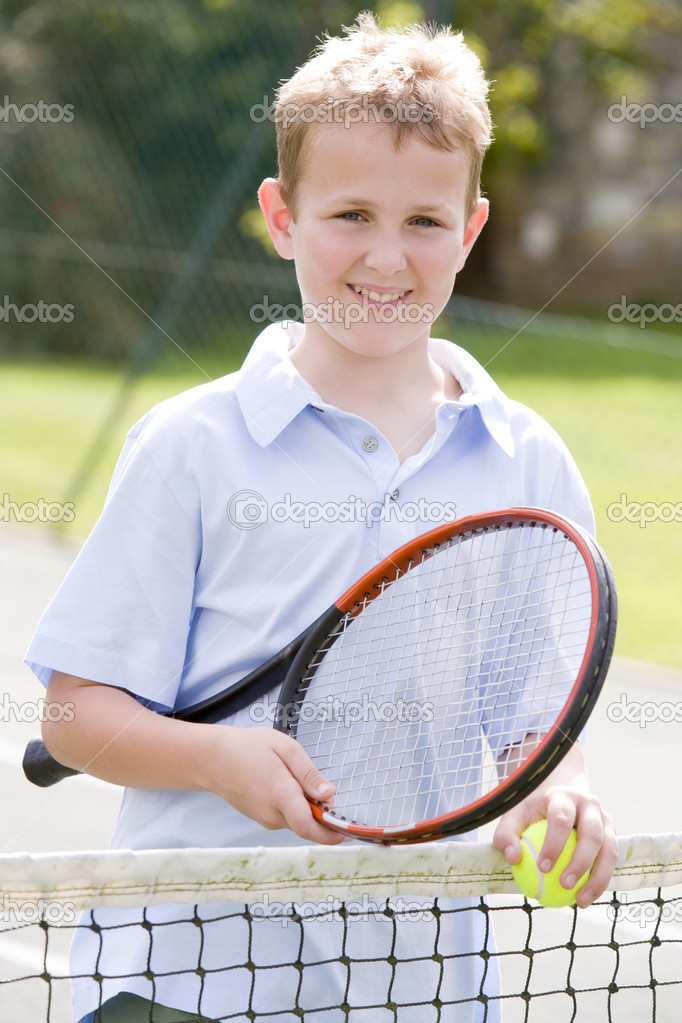 Young boy with racket on tennis court smiling — Stock Photo #4780009