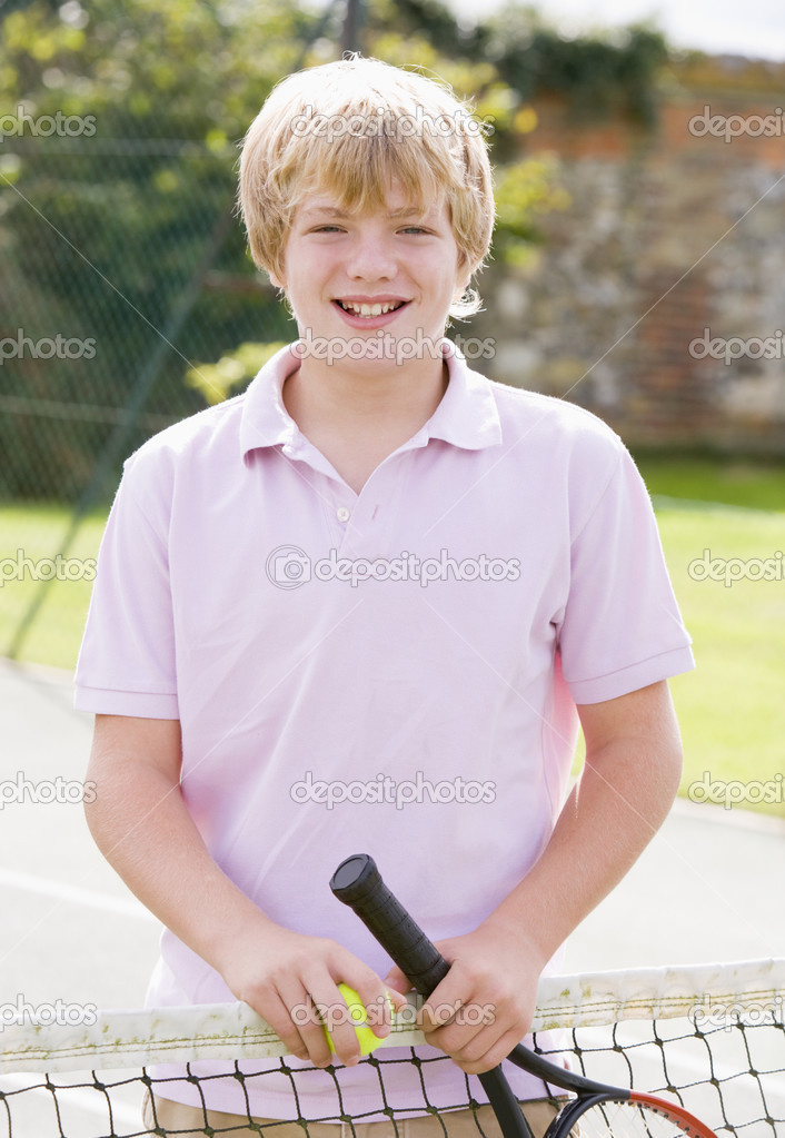 Young boy with racket on tennis court smiling  Stock Photo #4780014