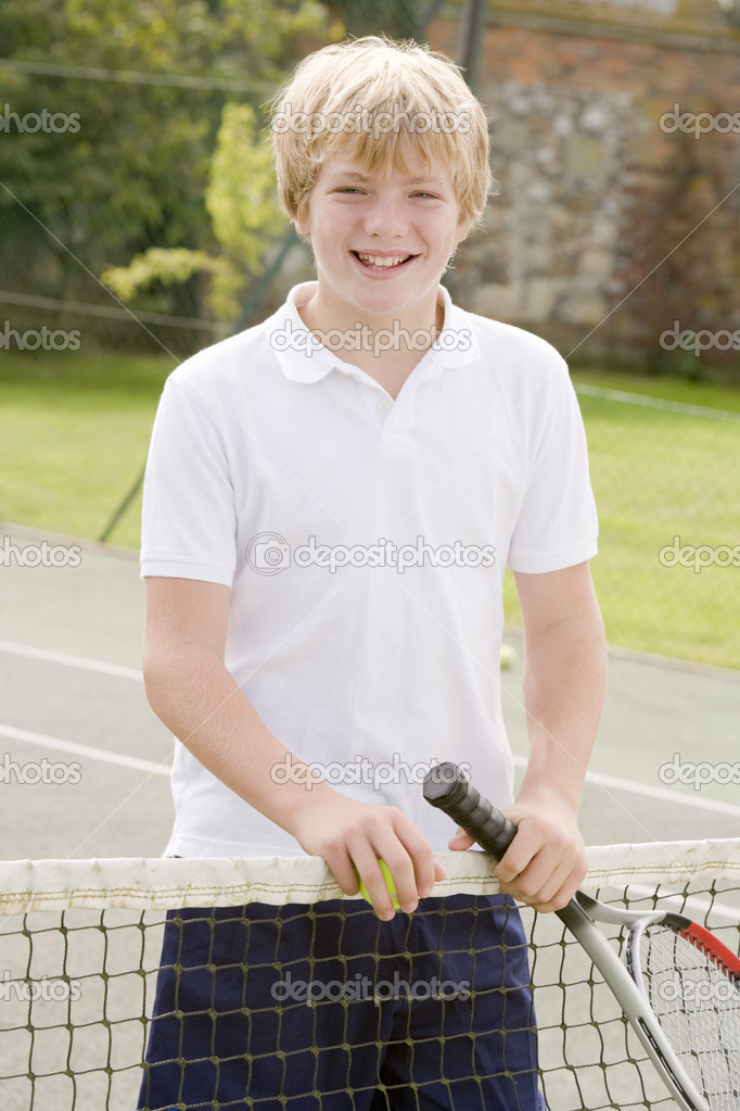 Young boy with racket on tennis court smiling — Stock Photo #4780031